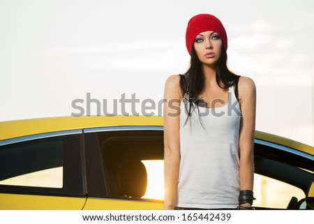 Fashionable young woman standing at the car - stock photo