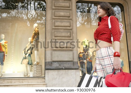 Fashionable young woman walking by a shop window, outdoors. - stock photo