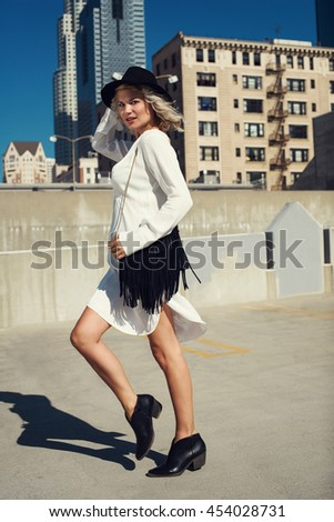 Fashionable young woman walking on the rooftop in the city wearing white shirt black hat and a handbag, boots. Fashion urban summer photo, blue sky