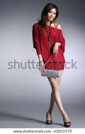 Fashionable young woman with handbag - stock photo