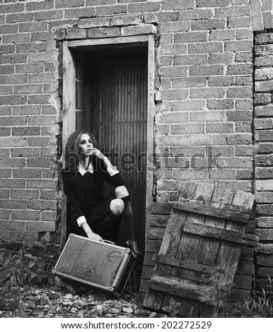 Fashionable young woman with her suitcase, old rural scene, black and white image