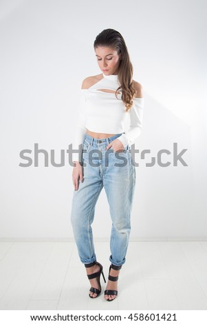 Fashionable Young Woman With Long Slicked Back Hair Wearing Jeans, White Blouse With Bare Shoulders And Black High Heeled Sandals With Straps Posing And Looking Down - stock photo