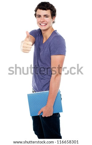 Fashionable youth with a notebook in hand showing thumbs up sign to the camera - stock photo