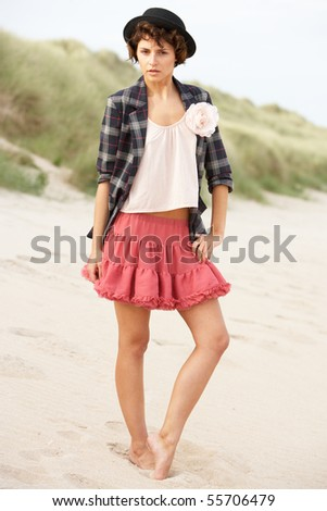 Fashionably Dressed Attractive Young Woman Standing Amongst Sand Dunes - stock photo