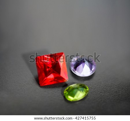 Fashioned ruby (red corundum), green chrysolite and amethyst on black background with vignette, a lot of space for text above gems. Synthetic precious stones macro shot. Selective focus
