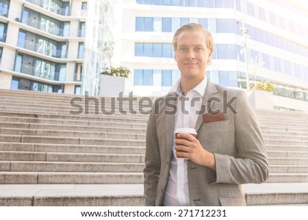 Fashioned young man in Oslo holding a cup of coffee with buildings on background. He has nordic facial features, and wearing a light gray suit.