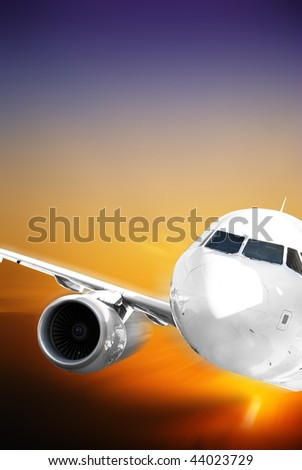 Fast airplane against colored sunset - stock photo