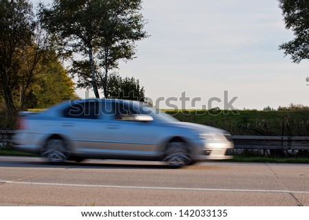 Fast blurry car at the highway - stock photo
