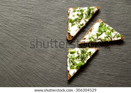 Fast canapes with soft cheese, parsley and dill on a dark background, top view, selective focus - stock photo