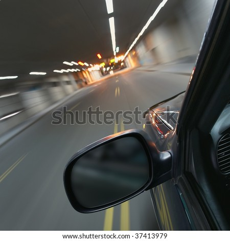 Fast car moving in motion through a tunnel - stock photo