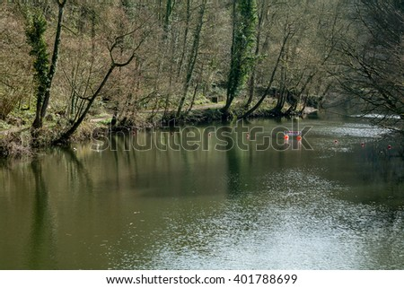 Fast flowing river with tree lined riverbank and danger sign - stock photo