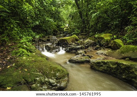 Fast flowing stream running through a rain forest in Costa Rica. - stock photo