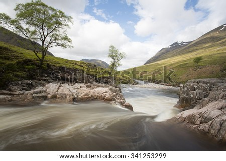 fast flowing water in a river in the mountains of scotland, glen etive - stock photo