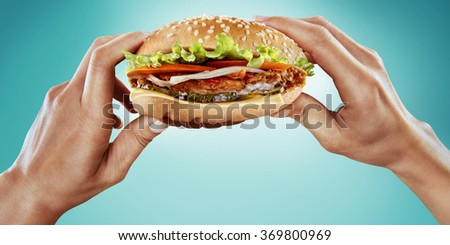 Fast food and diet. Hands hold the hamburger