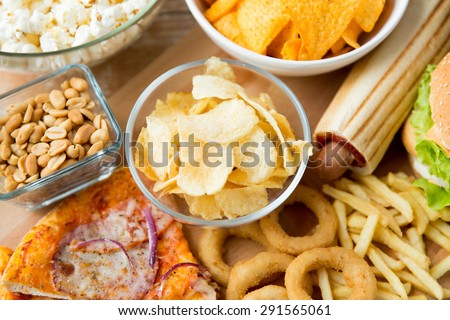 fast food and unhealthy eating concept - close up of different fast food snacks on wooden table - stock photo