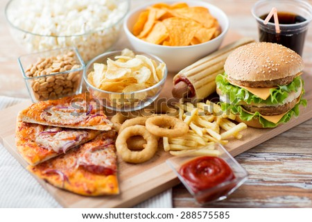 fast food and unhealthy eating concept - close up of fast food snacks and cola drink on wooden table - stock photo
