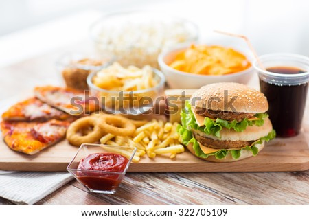 fast food and unhealthy eating concept - close up of hamburger or cheeseburger, deep-fried squid rings, french fries, drink and ketchup on wooden table - stock photo
