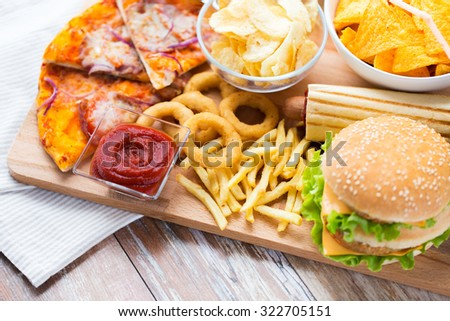 fast food and unhealthy eating concept - close up of hamburger or cheeseburger, deep-fried squid rings, french fries, pizza and ketchup on wooden table top view - stock photo