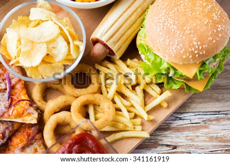 fast food and unhealthy eating concept - close up of hamburger or cheeseburger, deep-fried squid rings, french fries hotdog and potato chips on wooden table top view - stock photo