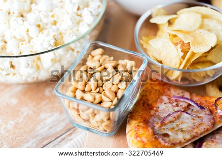 fast food and unhealthy eating concept - close up of peanuts in glass bowl, potato chips, pizza and popcorn on wooden table - stock photo