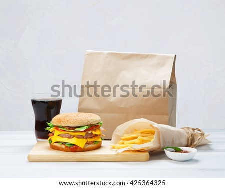 Fast food. Brown wrapping paper package with copyspace. Hamburger, potato fries, cola drink. Takeaway food. Wrapped French fries, packaging, Cola glass, tomato sauce, double cheese hamburger at wood. - stock photo
