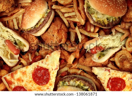 Fast food concept with greasy fried restaurant take out as onion rings burger and hot dogs with fried chicken french fries and pizza as a symbol of diet temptation resulting in unhealthy nutrition. - stock photo