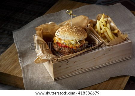 Fast food hamburger and french fries in a wooden box - stock photo