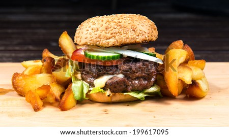 Fast food hamburger and french fries on a wooden plate - stock photo