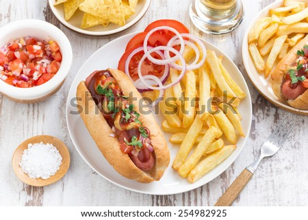fast food - hot dog with French fries and chips on wooden table, top view, horizontal - stock photo
