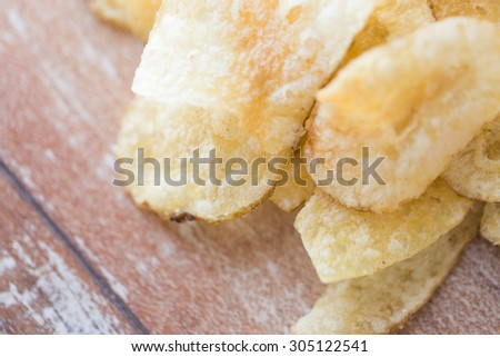 fast food, junk-food, cuisine and eating concept - close up of crunchy potato crisps on wooden table - stock photo