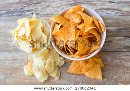 fast food, junk-food, cuisine and eating concept - close up of potato crisps and corn nachos in bowls on table - stock photo