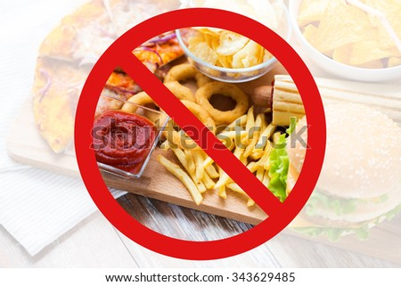 fast food, low carb diet, fattening and unhealthy eating concept - close up of deep-fried squid rings, french fries and other snacks behind no symbol or circle-backslash prohibition sign - stock photo