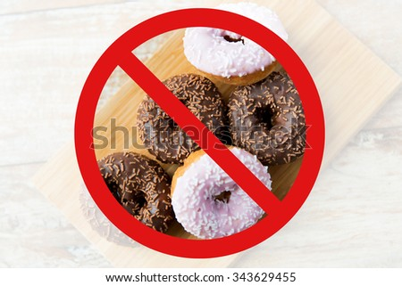 fast food, low carb diet, fattening and unhealthy eating concept - close up of glazed donuts on wooden board behind no symbol or circle-backslash prohibition sign - stock photo