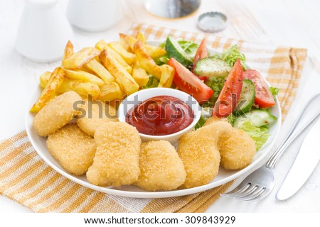 fast food lunch with chicken nuggets, french fries and vegetable salad on plate, horizontal - stock photo