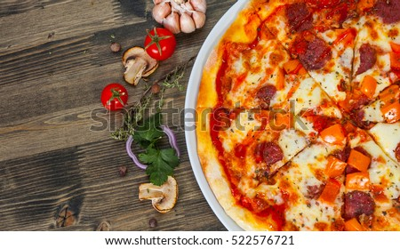 fast food. mexican pizza with pepperoni, vegetables, cheese on wood table with copy space. top view