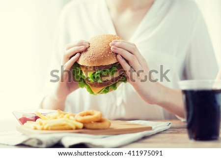 fast food, people and unhealthy eating concept - close up of woman hands holding hamburger or cheeseburger - stock photo