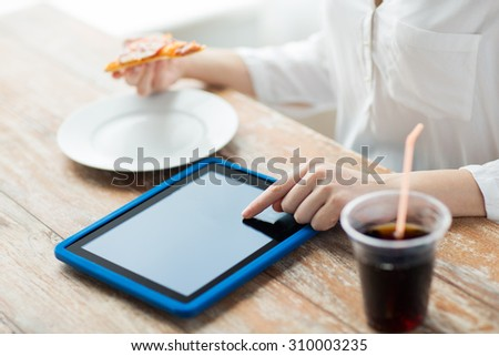 fast food, people, technology and diet concept - close up of woman with tablet pc computer, pizza and cola counting calories at table - stock photo