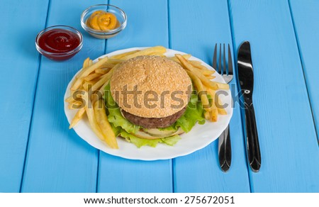 Fast food set of a burger, french fries and sauses on blue background - stock photo