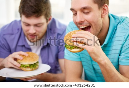 fast food, unhealthy eating, people and junk-food - close up of happy friends eating hamburgers at home - stock photo