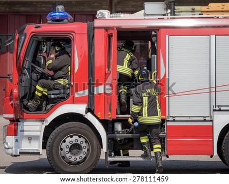 fast Italian firefighters climb on firetrucks during an emergency - stock photo