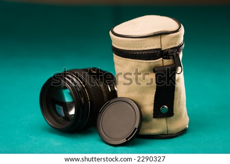 Fast lens with cap and pouch, on green background - stock photo
