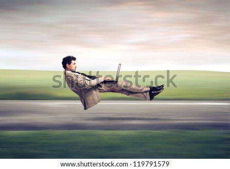 Fast levitating businessman, on a road, using a laptop computer - stock photo