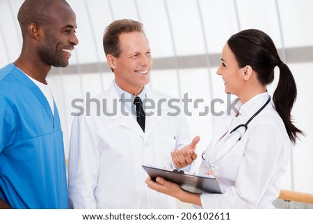 Fast meeting. Three confident doctors discussing something while woman holding clipboard and smiling