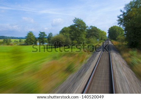 Fast motion blur on train tracks through green meadow - stock photo
