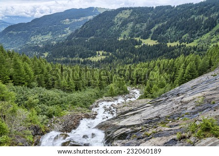 fast mountain river among green alpine forest - stock photo