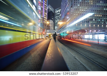 Fast moving bus lights blurred over modern city background - stock photo