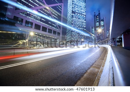 Fast moving cars lights blurred over modern city background - stock photo