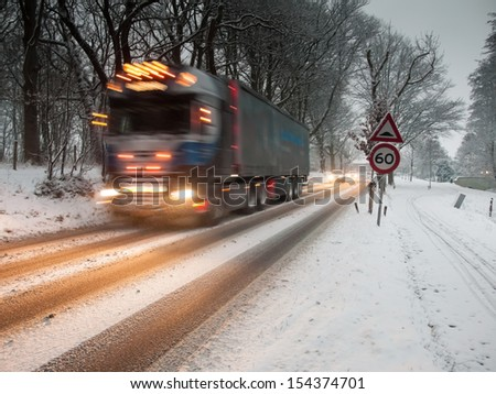 fast moving heavy goods vehicle passes a speed restriction sign in a snow storm under morning light - stock photo