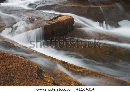 Fast moving mountain stream flowing over boulders in the White Mountains of New Hampshire - stock photo