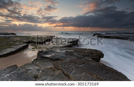 Fast moving ocean rock flows just after sunrise at the southern end of Turimetta rockshelf on Sydney's northern beaches. - stock photo